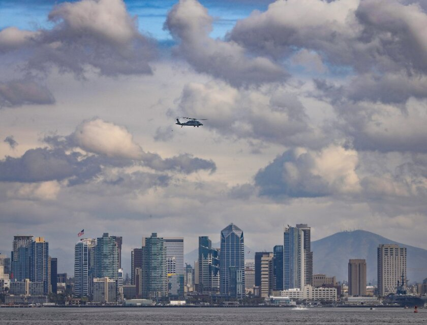 With the San Diego downtown skyline as backdrop, a Navy helicopter prepares to land at Naval Air Station North Island.