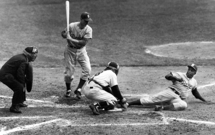 In this Sept. 28, 1955, photo, the Brooklyn Dodgers' Jackie Robinson safely steals home plate under the tag of New York Yankees catcher Yogi Berra in the eighth inning of the World Series opener at New York's Yankee Stadium. Berra, who played in more World Series games than any other major leaguer and was a three-time American League Most Valuable Player, died Tuesday at the age of 90.