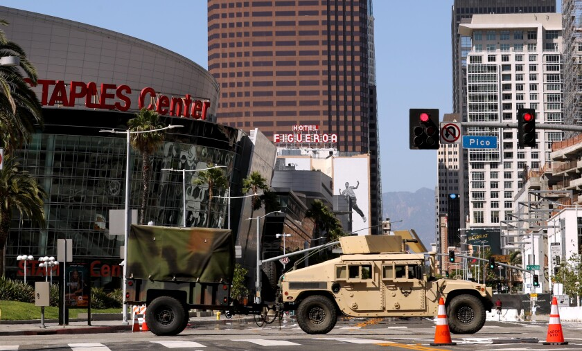 A military vehicle crosses Figueroa Street on Sunday as California National Guardsmen leave the Convention Center in L.A.