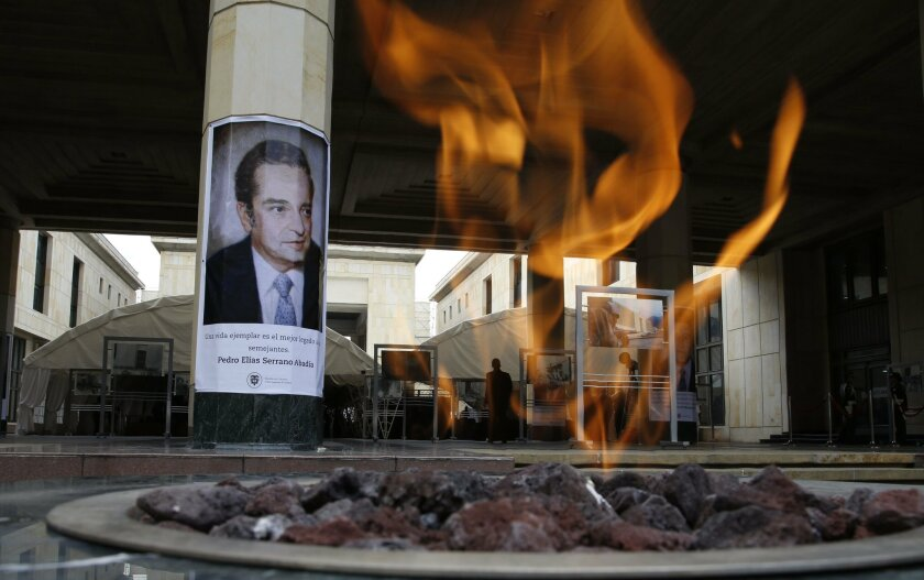 A memorial flame burns at the rebuilt Palace of Justice on the 30th anniversary of a deadly government siege in Bogota, Colombia, Friday, Nov. 6, 2015. The poster on the wall shows Pedro Elias Serrano, a judge who died in the siege. Rebels from the now-defunct insurgency known as M-19 took the high
