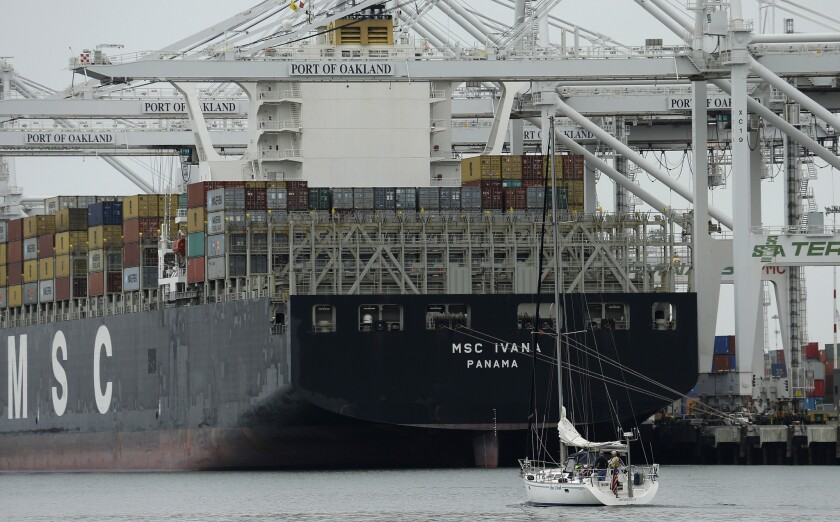 A sailboat makes its way past the container ship MSC Ivana as she is unloaded at the Port of Oakland. U.S. exports would grow under the Trans-Pacific agreement, a report says.