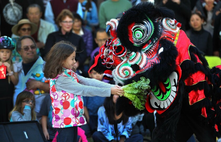 Hannah Bolanos-Roth gives lettuce to one of the lions from the Three Treasures Cultural Arts Society Lion dancers.