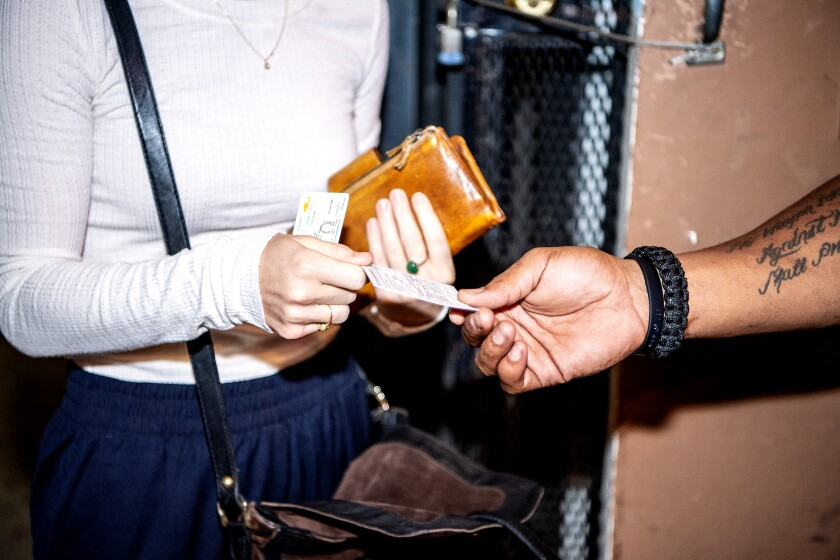 A woman holds out a card as a man's hand grasps it