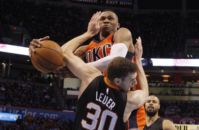 Oklahoma City Thunder guard Russell Westbrook, rear, collides with Phoenix Suns forward Jon Leuer (30) in the second quarter of an NBA basketball game in Oklahoma City, Sunday, Nov. 8, 2015. (AP Photo/Sue Ogrocki)