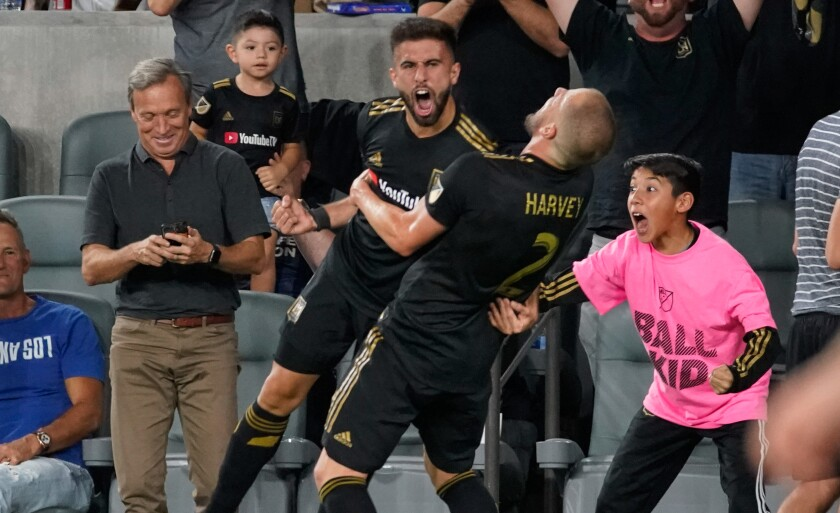 LAFC forward Diego Rossi, left, celebrates with defender Jordan Harvey after scoring during a 5-3 playoff win over the Galaxy on Thursday.