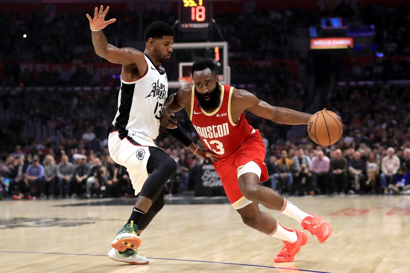 Clippers forward Paul George tries to cut off a drive by Rockets guard James Harden during their game Nov. 22, 2019, at Staples Center.