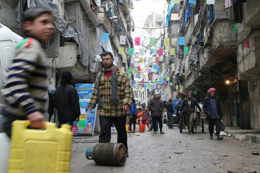 FILE - In this Thursday, Feb. 11, 2016 file photo, civilians carry supplies in Aleppo, Syria. Syrian government troops who have besieged dozens of rebel-held communities over the past three years are moving toward their biggest target yet–opposition-controlled neighborhoods of the city of Aleppo, w
