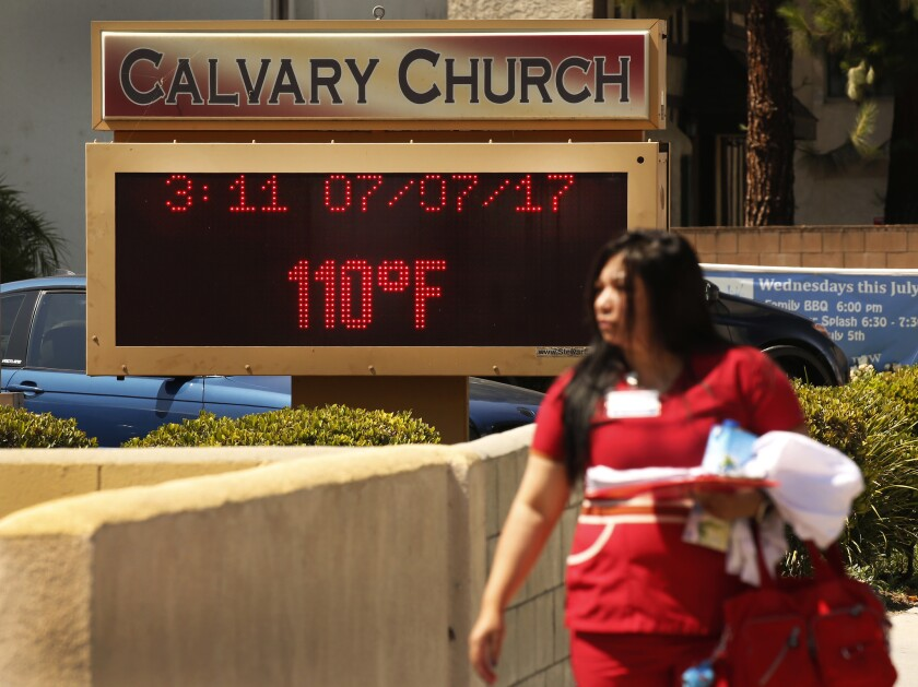 People brave record 110-degree temperatures Friday while walking to work in West Hills in the San Fe