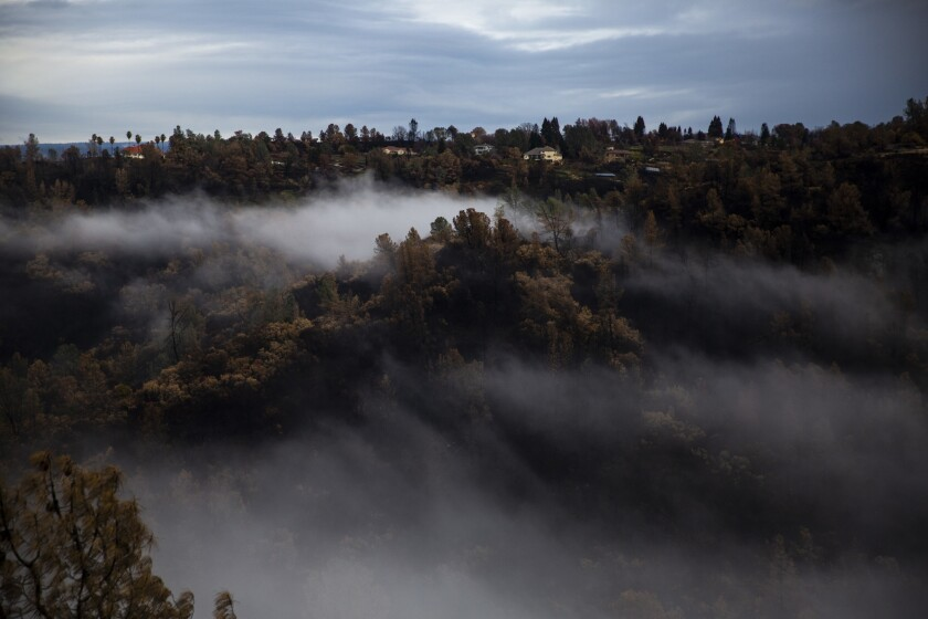 PARADISE, CALIF. - DECEMBER 15: Fog creeps up over a Camp Fire burn area along Butte creek, viewed