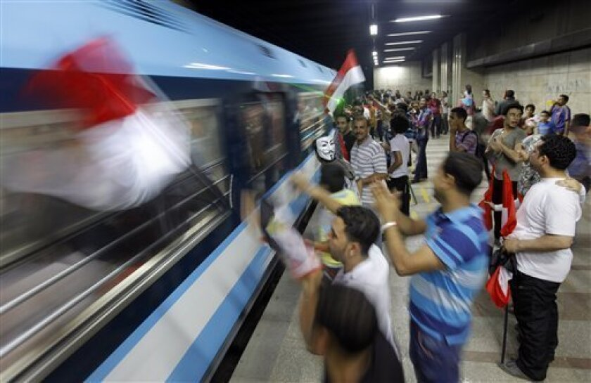 In this image made late Wednesday, July 3, 2013, opponents of Egypt's Islamist leader Mohammed Morsi wave national flags to a passing underground train as they celebrate Morsi's ouster in Cairo, Egypt. The chief justice of Egypt's Supreme Constitutional Court was sworn in Thursday as the nation's interim president, taking over hours after the military ousted the Islamist President Mohammed Morsi. Adly Mansour took the oath of office at the Nile-side Constitutional Court in a ceremony broadcast l