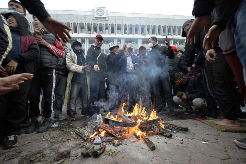 Protesters gather around a fire set in the street in front of the Kyrgyz government headquarters