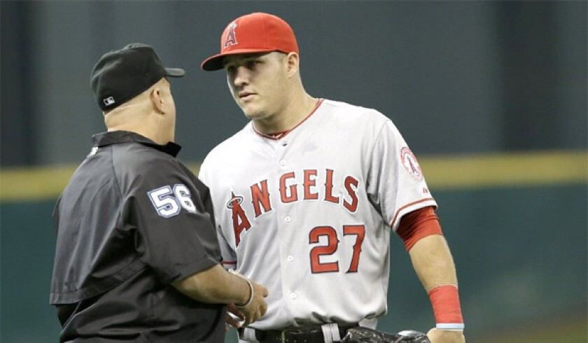 Angels outfielder Mike Trout talks with umpire Eric Cooper during the first inning of a game against the Houston Astros on April 6.