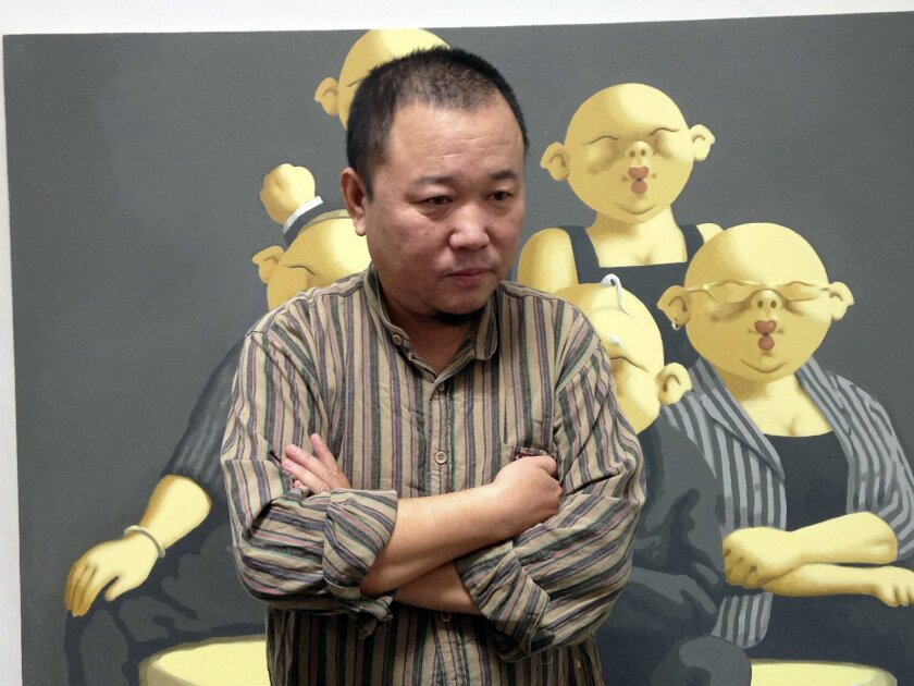 In this photo taken Sept. 20, 2014, Chinese artist Li Dapeng talks to reporters in front of one of his works depicting a typical Chinese scene featuring figures with grotesque pig heads at his studio in the Songzhuang art district in eastern Beijing, China. Artists in Songzhuang have long enjoyed r