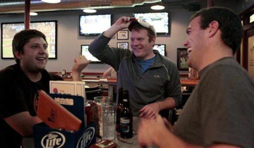 In this photo taken, Thursday, Oct. 7, 2010, sports fans Tyler Zimmer, Justin Wells and T.J. Erlacker talk football over drinks at The Post Bar and Grill in Maplewood, Mo. Many sports fans around Missouri are more excited this year because their teams, from the surprising Chiefs to the promising Rams and the ranked Tigers, are actually watchable. (AP Photo/Jeff Roberson)