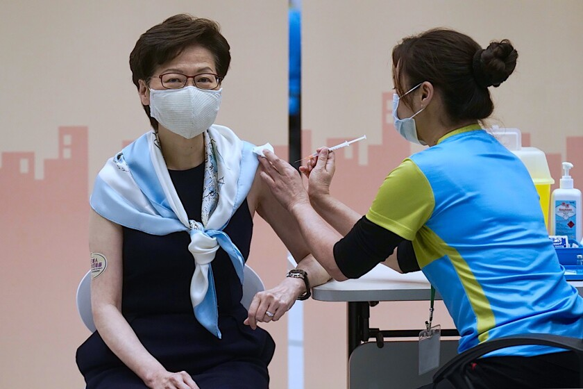 FILE- In this Monday, March. 22, 2021, file photo, Hong Kong Chief Executive Carrie Lam receives the second dose of the Sinovac Biotech COVID-19 vaccine at a Central Government office in Hong Kong. Hong Kong's sudden suspension of a COVID-19 vaccine developed by Pfizer and BioNTech is another blow to a vaccination program already struggling against a wall of public distrust. Hong Kong on Wednesday, March 24, 2021, suspended use of the Pfizer vaccine, distributed by Chinese pharmaceutical firm Fosun Pharma, after defective packaging such as loose vial lids and cracks on bottles were found in one of two batches of the vaccine. (AP Photo/Vincent Yu, File)
