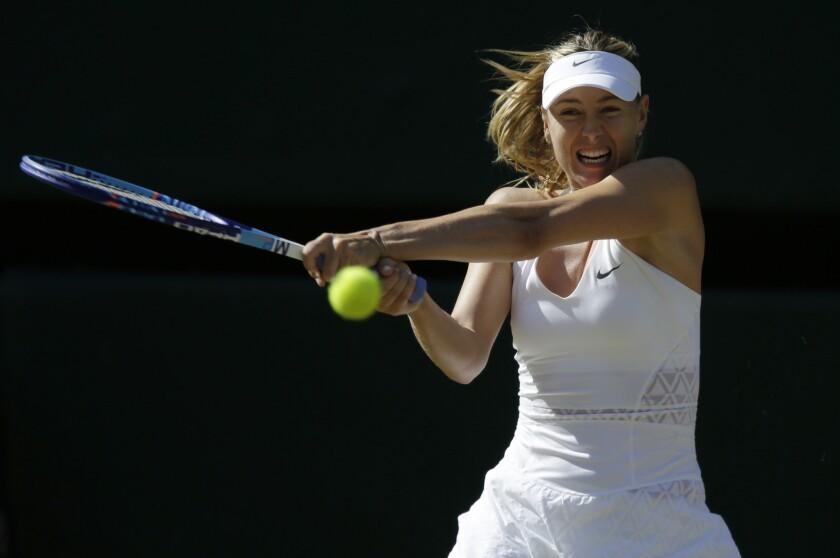 Maria Sharapova returns a shot against Serena Williams during a women's singles semifinal match Wimbledon