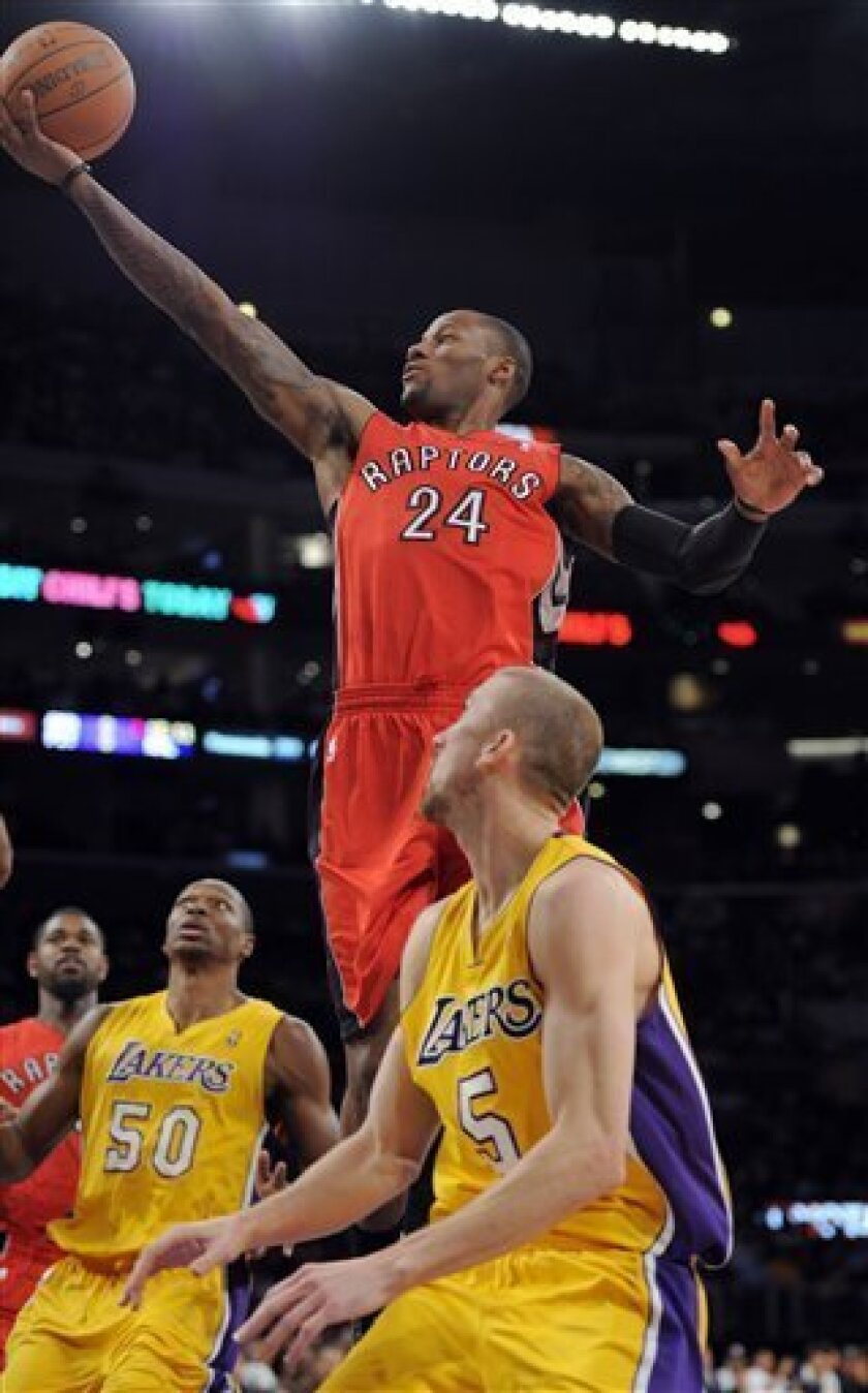 Toronto Raptors guard Sonny Weems, top, goes up for as shot as Los Angeles Lakers center Theo Ratliff, left, and guard Steve Blake look on during the first half of their NBA basketball game, Friday, Nov. 5, 2010, in Los Angeles. (AP Photo/Mark J. Terrill)