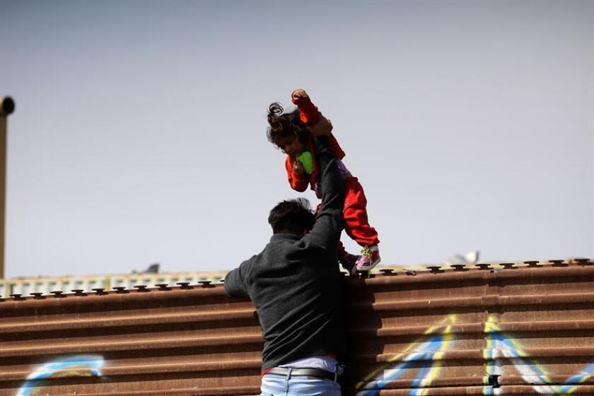Un hombre lanzaba a su hija a territorio norteamericano por la valla fronteriza que separa México de Estados Unidos, en el punto denominado Las Torres, en el estado de Tijuana, el pasado 12 de marzo. EFE/Archivo