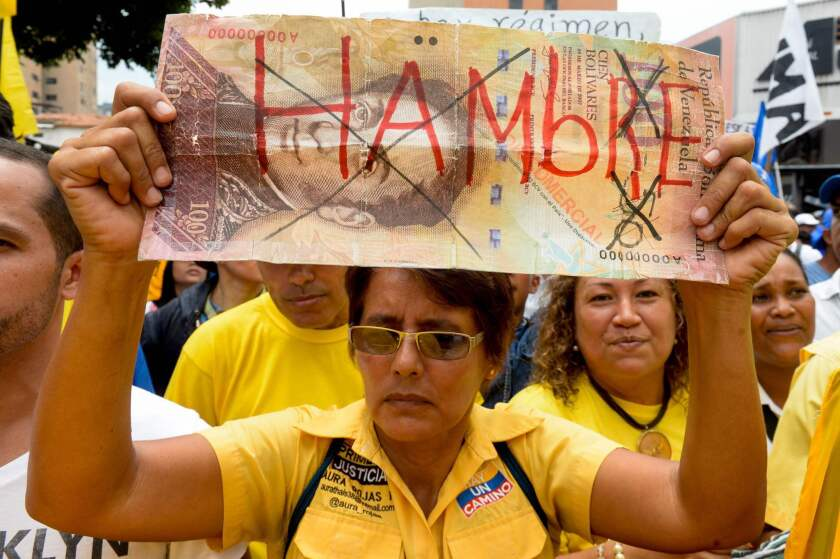 """A woman holds a sign reading """"Hunger"""" during a demonstration in Caracas, Venezuela, on May 14, 2016."""