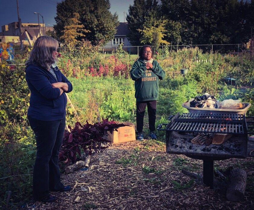 Venice Williams, right, stands and peaks in a community garden as another woman watches.