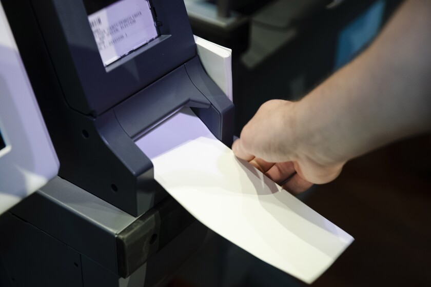 """FILE—In this June 13, 2019 file photo, an Investigator with the Office of the City Commissioners, demonstrates the ExpressVote XL voting machine at the Reading Terminal Market in Philadelphia. As the Nov. 3 2020 presidential vote nears, there are fresh signs that the nation's electoral system is again under attack from foreign adversaries. Intelligence officials confirmed in recent days that foreign actors are actively seeking to compromise the private communications of """"U.S. political campaigns, candidates and other political targets"""" while working to compromise the nation's election infrastructure. (AP Photo/Matt Rourke, File)"""