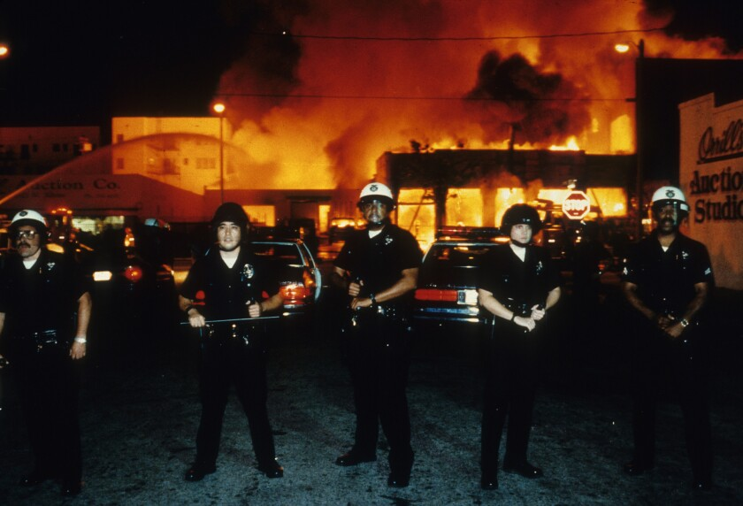 Officers stand guard as fire units battle a blaze near 19th Street and Adams Boulevard on April 30, 1992.