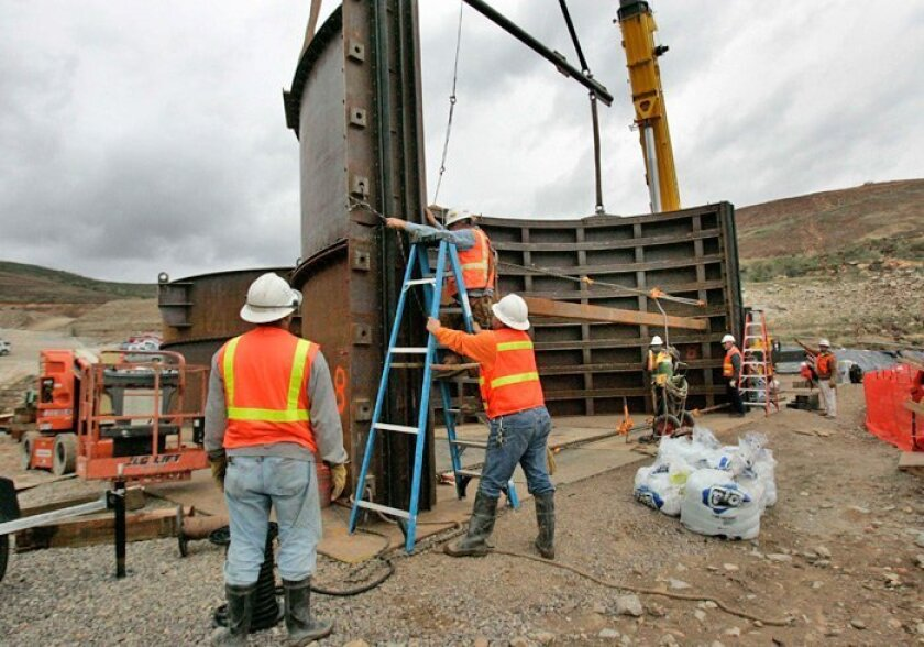 Ironworkers prepared to bolt together two sections of a cofferdam last week before taking it to San Vicente Dam, which is being built under the San Diego County Water Authority's project labor agreement.