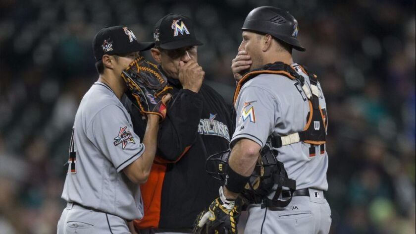Marlins pitcher Wei-Yin Chen meets with pitching coach Juan Nieves and catcher A.J. Ellis on the mou