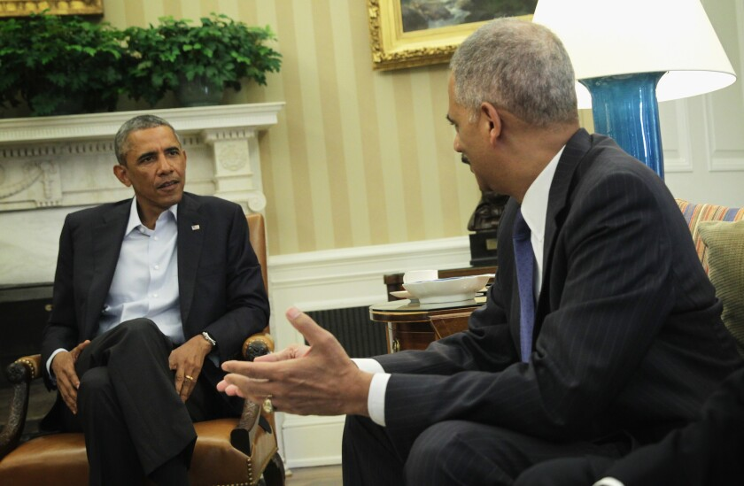 President Obama, left, is seen meeting with Attorney General Eric Holder in the Oval Office of the White House on Aug. 18, 2014.