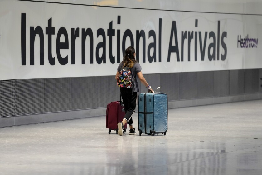 In this Monday, Aug. 2, 2021 file photo, a passenger arrives from a flight at Terminal 5