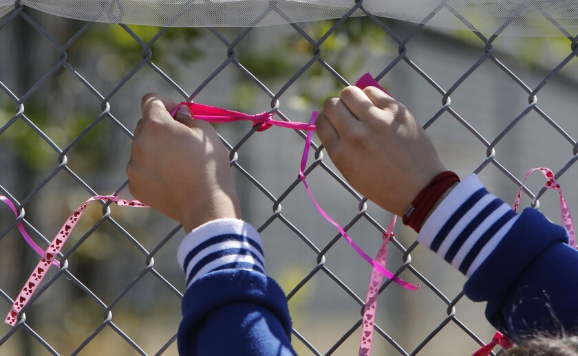 A student at Jenny Lind Elementary School ties a ribbon honoring murder victim Leila Fowler.