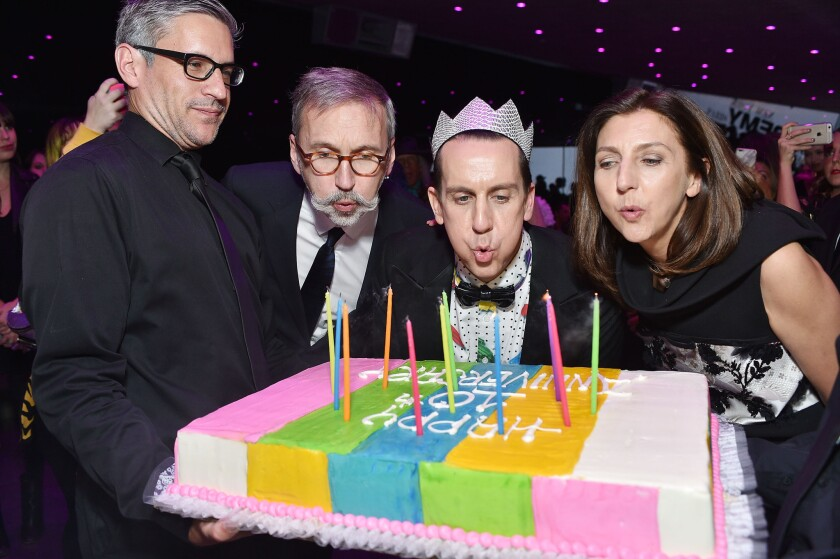 "Longchamp Chief Executive Officer Olivier Cassegrain, second from left, designer Jeremy Scott, center, and Longchamp artistic director Sophie Delafontaine blow out the candles on a cake decorated with ""Happy 10th Anniversary"" at party in the Hollywood Hills."