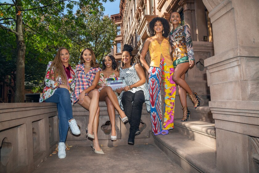 """The cast and creatives of """"Run the World"""" on a New York stoop."""