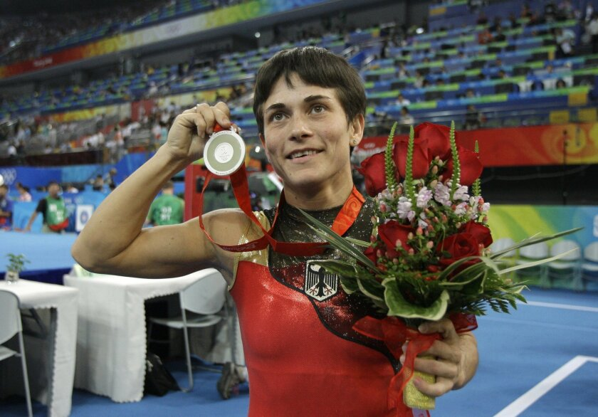 FILE - In this Aug. 17, 2008 file photo Germany's gymnast Oksana Chusovitina poses after winning the silver medal during the women's vault apparatus finals at the Beijing 2008 Olympics in Beijing. Chusovitina will compete at her seventh Olympics when she goes to Rio de Janeiro, becoming the oldest Olympic female gymnast in history at age 41. (AP Photo/Amy Sancetta, file)