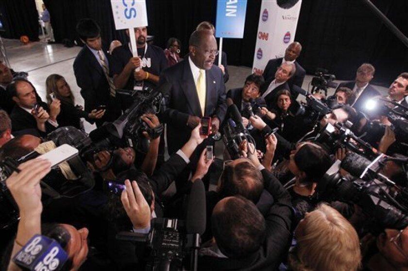 Republican presidential candidate Herman Cain speaks with members of the press following a Republican presidential debate Tuesday, Oct. 18, 2011, in Las Vegas. (AP Photo/Isaac Brekken)