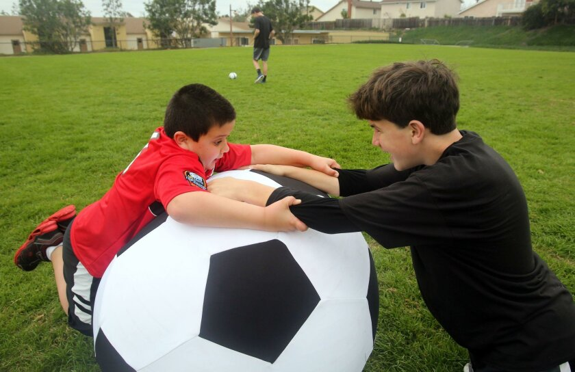 """Champions League volunteer """"buddy"""" Aidan Cohen, 13, right, plays with Dominic Pasqueralli, 9, on a giant soccer ball Saturday at Ada Harris Elementary School in Cardiff. Dominic is one of the special-needs players served by the just-launched Champions League."""