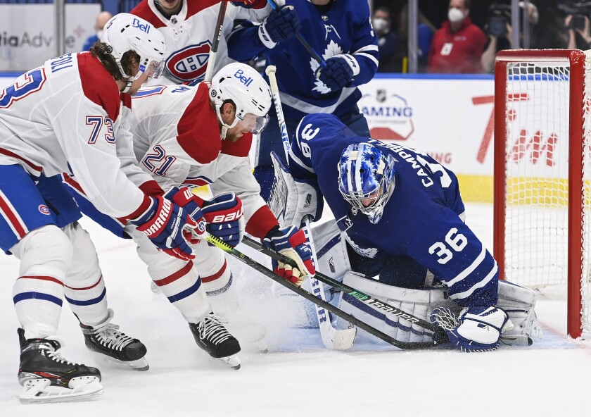 Montreal Canadiens forward Eric Staal (21) and teammate Tyler Toffoli (73) poke at the covered puck under Toronto Maple Leafs goaltender Jack Campbell's glove during the second period of an NHL hockey game Wednesday, April 7, 2021, in Toronto. (Nathan Denette/The Canadian Press via AP)