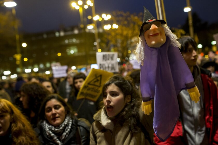 """People, one of them holding a puppet, gather outside Madrid city hall in support of two puppeteers who were detained without bail last Friday for using a sign saying, """"Long Live Alka ETA,"""" in a word-play reference to Spain's armed Basque group ETA and al-Qaida, in Madrid, Wednesday, Feb. 10, 2016."""