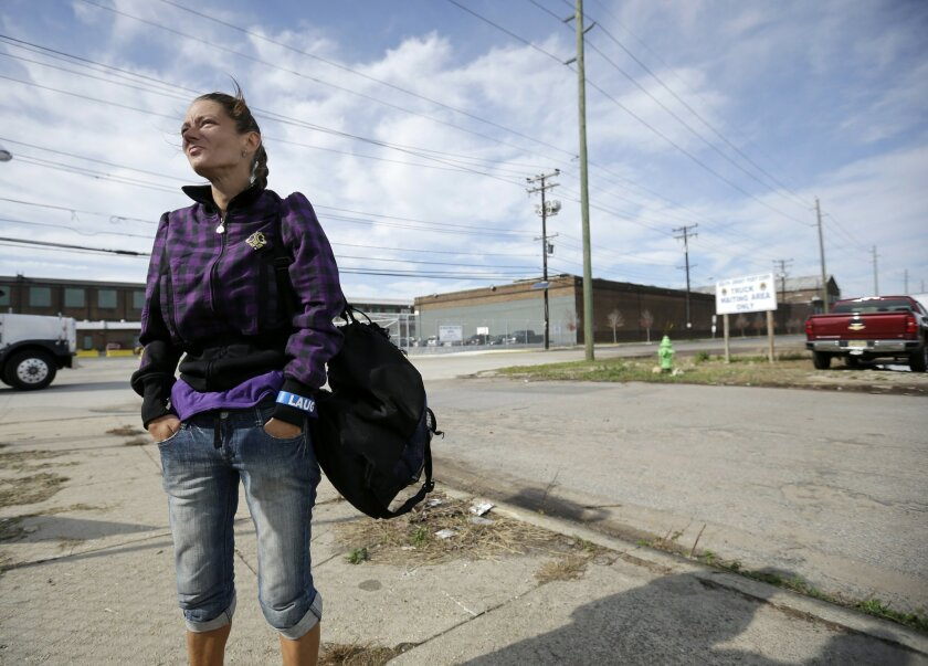 In this Thursday, Oct. 29, 2015 photograph, Billie Fisher stands in an industrial area of Camden, N.J., as she talks about being given the drug naloxone a couple years ago, to reverse a heroin overdose.  Fisher said after being given the drug, she was in an emergency room in painful withdrawal.  Na