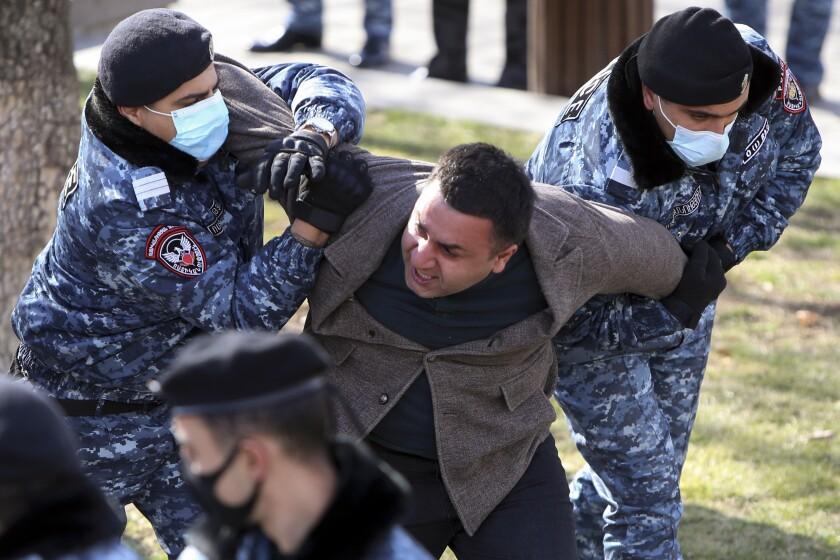 La policía detiene a un manifestante opositor durante una protesta contra el gobierno en la sede de gobierno en Ereván, Armenia, el martes 23 de febrero de 2021. Cientos de personas se reunieron en la capital armenia para pedir la renuncia del primer ministro, Nikol Pashinyan. (Hayk Baghdasaryan/PHOTOLURE via AP)