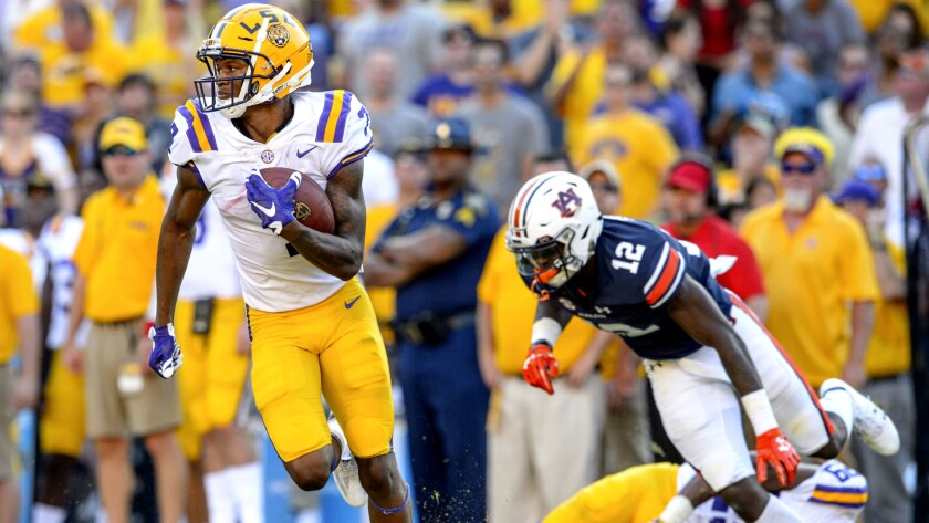 LSU wide receiver D.J. Chark (7) returns a punt for a touchdown as cornerback Andraez Williams (29)