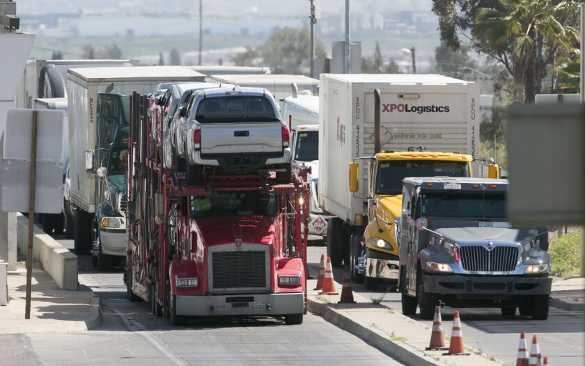 Trucks drive over the scales at the Otay Mesa commercial port of entry in San Diego Monday.