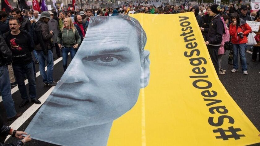 Protesters hold a poster with the image of political prisoner Oleg Sentsov at a Moscow rally June 10.
