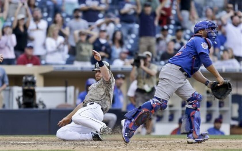 San Diego Padres' Logan Forsythe slides in safely with the game winning run as Chicago Cubs catcher Welington Castillo chases the late throw in the fifteenth inning of a baseball game won 3-2 by the Padres Sunday, Aug. 25, 2013, in San Diego. (AP Photo/Lenny Ignelzi)