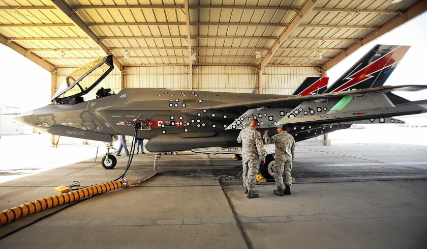 A Lockheed Martin F-35 Joint Strike Fighter is prepared for flight during testing at Edwards Air Force Base in March 2013. The numerous decals fixed to the side of the jet are used to monitor flight and payload performance by video.
