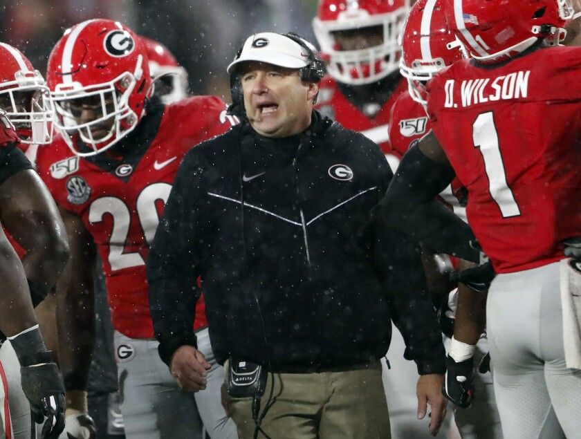 FILE - In this Oct. 19, 2019, file photo, Georgia coach Kirby Smart, center, talks to his players during a timeout in the first half of the team's NCAA college football game against Kentucky in Athens, Ga. There will be much interest in possible changes coming to No. 4 Georgia's offense with a new quarterback, who is expected to be Wake Forest transfer Jamie Newman, and a new coordinator, Todd Monken. Still, Smart's Bulldogs may lean on their experienced defense in the pandemic-delayed season. (AP Photo/John Bazemore, File)