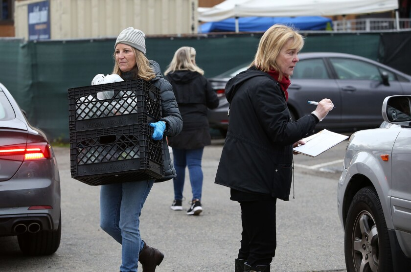 Anne Belyea, Lesli Henderson and Susan Thomas, from left, organize cars and get information from visitors receiving goods during drive-up distribution at the Laguna Food Pantry on Wednesday.