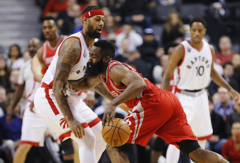 Houston Rockets' James Harden, right, is guarded by Toronto Raptors' James Johnson during first half NBA basketball action in Toronto on Sunday, March 6, 2016. (Mark Blinch/The Canadian Press via AP)
