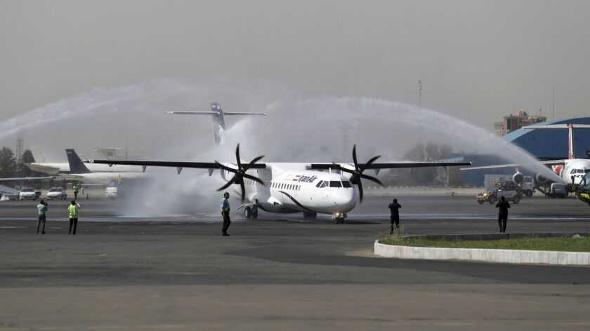 In this photo provided by Tasnim News Agency, a traditional water cannon salute welcomes an Iran Air