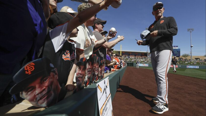 San Francisco Giants manager Bruce Bochy, right, gives autographs before a spring baseball game agai